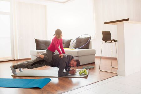 father and daughter are training at home. Workout in the apartment. Sports in home conditions. They make the doing plank. daughter climbed on dad. He is pushing up from the floor.