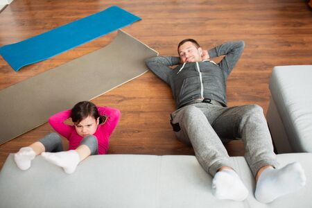 father and daughter are doing abs training at home. Workout in the apartment. Sports training in the living room Фото со стока
