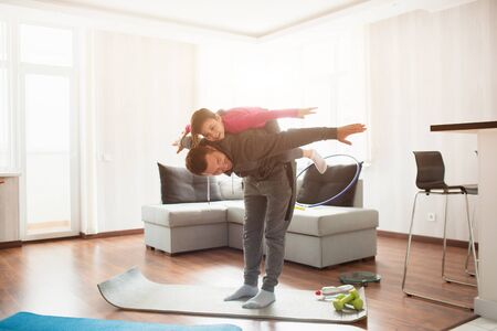 father and daughter are training at home. Workout in the apartment. Sports at home. Daughter climbed on her back and has fun.