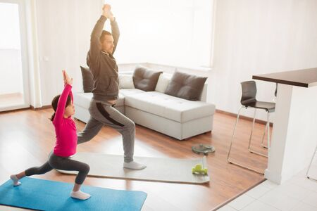 Little girl and her young father are doing lunge forward workout at home. Cute kid is training indoor. Little dark-haired female model in sportswear has exercises in room. Фото со стока