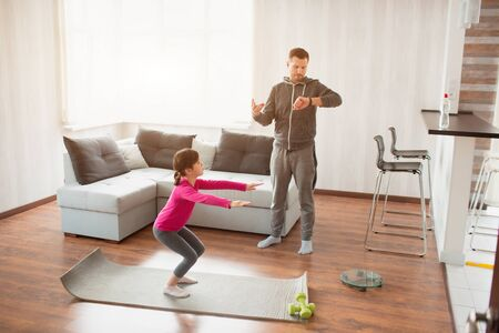 father and daughter are training at home. Workout in the apartment. Sports at home. Daddy uses a sports watch And daughter is doing Squat Exercises 版權商用圖片 - 147770574
