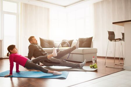 father and daughter are training at home. Workout in the apartment. Sports at home. Rreverce plank with leg raise on the floor at home 版權商用圖片
