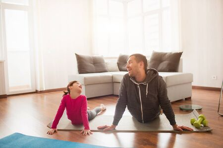 father and daughter are training at home. Workout in the apartment. Sports at home. They make faces and have fun on a yoga mat 版權商用圖片