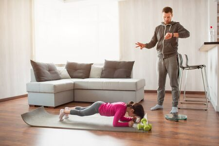 father and daughter are training at home. Workout in the apartment. Sports at home. Daddy uses a sports watch And daughter is doing plank. Фото со стока