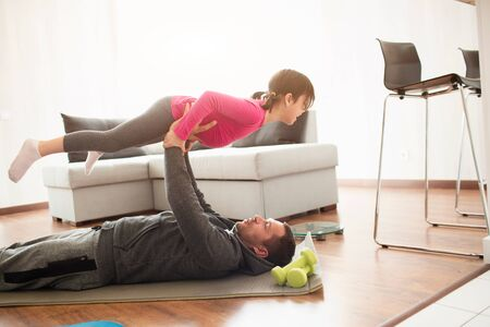 father and daughter are training at home. Workout in the apartment. Sports at home. Daddy lies on a yoga mat, and holds his daughter in his arms.
