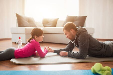 father and daughter are training at home. Workout in the apartment. Sports at home. Compete in arm wrestling and lie on a yoga mat