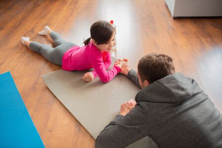 father and daughter are training at home. Workout in the apartment. Sports at home. Compete in arm wrestling and lie on a yoga mat 版權商用圖片 - 147770100