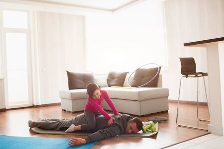 father and daughter are training at home. Workout in the apartment. Sports at home. Dad is very tired. Daughter climbed on her back and has fun. 版權商用圖片 - 147770112