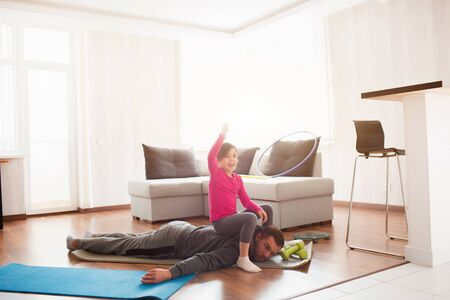 father and daughter are training at home. Workout in the apartment. Sports at home. Dad is very tired. Daughter climbed on her back and has fun.