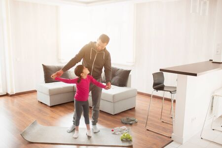 father and daughter are training at home. Workout in the apartment. Sports at home. They are standing on a yoga mat.