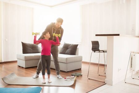 father and daughter are training at home. Workout in the apartment. Sports at home. They are standing on a yoga mat. Girl holding dumbbell 版權商用圖片 - 147770518
