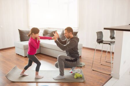 father and daughter are training at home. Workout in the apartment. Sports at home. Father teaches to keep a punch. Boxing together. Boxing training at home 版權商用圖片