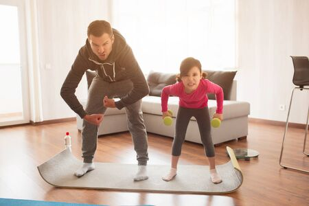 father and daughter are training at home. Workout in the apartment. Sports at home. They make faces and have fun on a yoga mat with dumbbells.