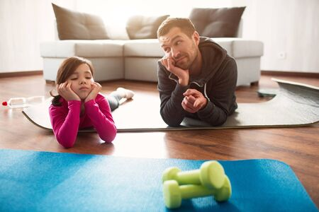 father and daughter are training at home. Workout in the apartment. Sports at home. They make faces and have fun on a yoga mat and look at dumbbells.