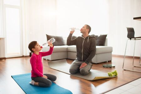 father and daughter are training at home. Workout in the apartment. Sports at home. They sit on yoga mats and drink water. You need clean water to drink your sport time. 版權商用圖片 - 147770587