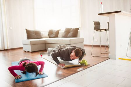 father and daughter are training at home. Workout in the apartment. Sports at home. They push up on the floor together on yoga mats. 版權商用圖片 - 147770536