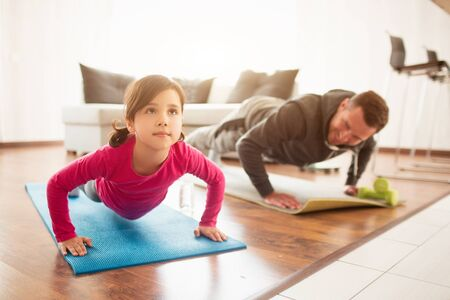 father and daughter are training at home. Workout in the apartment. Sports at home. They push up on the floor together on yoga mats.