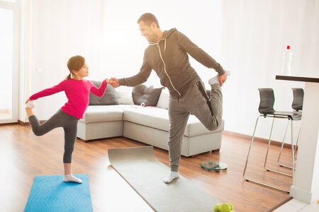 father and daughter are training at home. Workout in the apartment. Sports at home. They do exercises with yoga or Pilates. Фото со стока