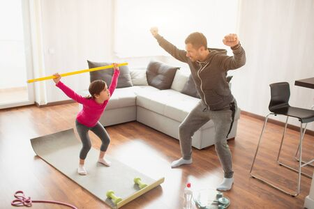 father and daughter are training at home. Workout in the apartment. Doing squat exercises workout at home. Cute kid and daddy are training on a mat indoor near the window in her room