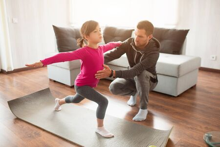 Little girl and her young father are doing lunge forward workout at home. Cute kid is training indoor. Little dark-haired female model in sportswear has exercises in room