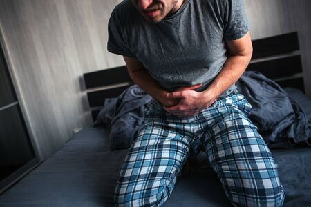 A man sits on a bed in his pajamas and holds on to his stomach. Diarrhea, indigestion, cramping and stomach pain. 스톡 콘텐츠
