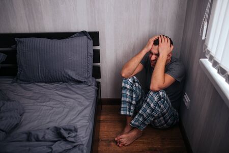 Depression, panic attack concept. A man is sitting in a corner near the bed. He feels bad.