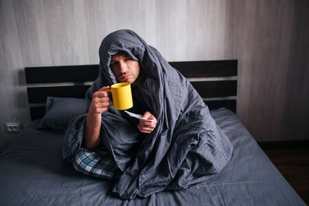 The man got sick. Lies in bed and suffers. He has fever, flu, colds and snot. He covered himself with a blanket and holds a napkin and hot tea.