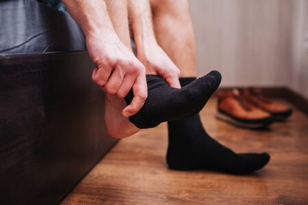 Close-up. A man puts a sock on the background of shoes. He is sitting on his bed. 版權商用圖片