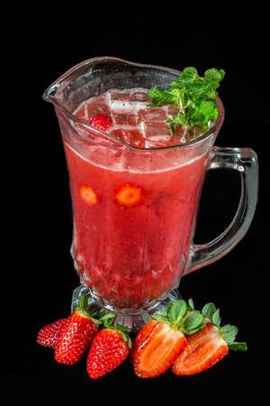 pitcher of sparkling wine and strawberry on black background. Reklamní fotografie