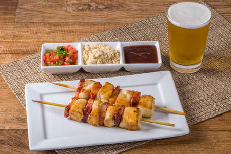 chicken skewers on wooden table.