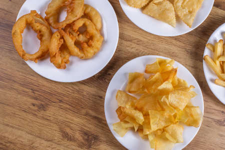 Mixed fried snacks on the table. French fries, onion rings and fries. Stok Fotoğraf