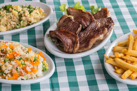 Picanha, a traditional Brazilian cut of meat, French fries, colored rice and farofa.