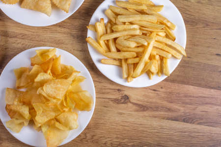 portion of potato chips and french top view on wooden background. Stok Fotoğraf