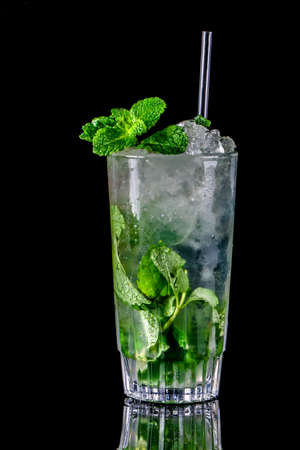 Glass of mojito with mint on black background.