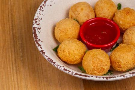 Delicious cheese ball with sauce. Brazilian snack, called a bolinha de queijo.