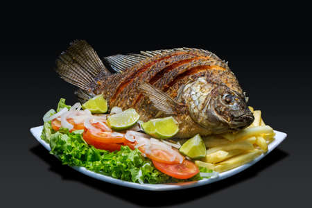 Fried whole fish with tomato and onion salad, on black background.