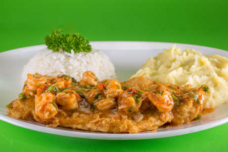 breaded fish dish with shrimp sauce, white rice and mashed potatoes on green background. Stok Fotoğraf