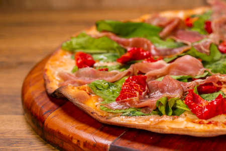 pizza with arugula with sun-dried tomatoes and parma ham on wooden background. Stock Photo