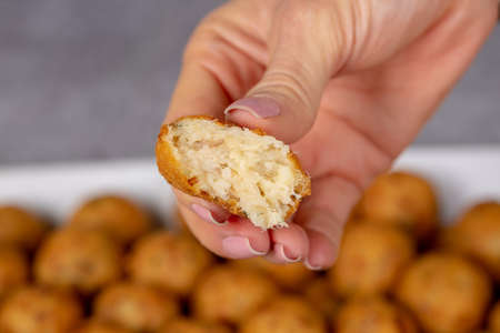croquette made from potatoes with cod is a traditional Portuguese dish in Brazil called bolinho de bacalhauhand holding bitten cod dumpling with blurred background.