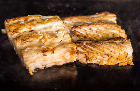 delicious pieces of cod fillet that cook on a hot plate.