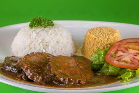rosbif con arroz y ensalada sobre fondo verde es un plato tradicional de la cocina brasileña. Foto de archivo