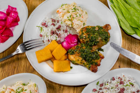 typical food from southern Brazil. A small chicken called galeto served with herbs, potato salad, fried polenta, rice with dried meat called carreteiro rice and wine onion Stok Fotoğraf