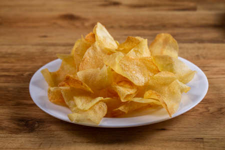 portion of potato chips on wooden background.