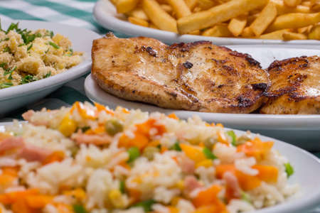 grilled chicken breast, french fries, colorful rice and farofa served on a table with green and white checkered tablecloth.