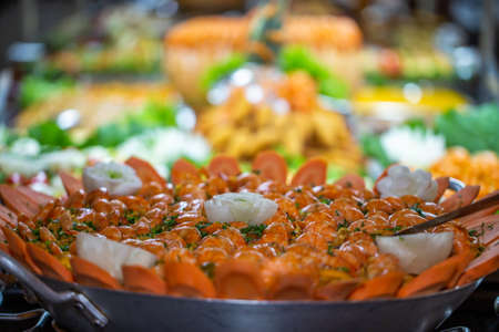 seafood paella on the foreground with defocused restaurant food buffet in the background.