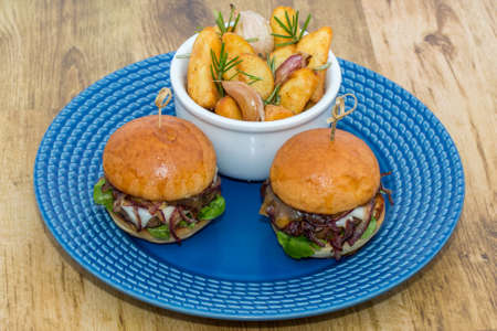 Delicious mini hamburgers served with potato with rosemary and garlic in blue crockery on wooden background. Stok Fotoğraf