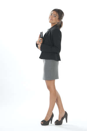 Sideview of self confident female young business executive with notebook, looking at camera