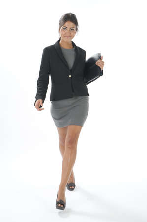 Female young business executive walking with notebook in her hands
