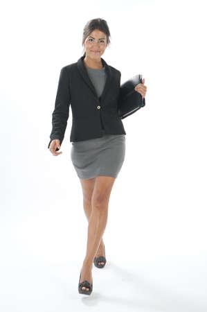 attractiveness: Mujer de negocios ejecutiva joven que camina con el cuaderno en sus manos
