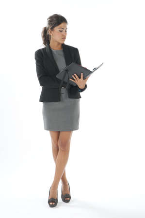 Serious portrait of self confident female young business executive, looking at her notebook. Stock Photo - 14429475